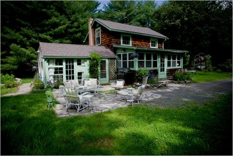 Christina Salway and John Moskowitz spent weekends from October to May renovating their 700-square-foot 1920s cottage in Sparrow Bush, N.Y., their first home purchase. A converted garage on the left is now a living room that has been enclosed with salvaged windows and glass-paned doors.