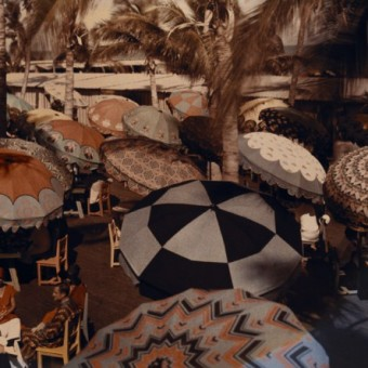 Club members on the ocean front are shaded by decorative parasols.